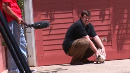 Dude shamelessly petting a cat in the Behind the Scenes of Kayden Exposed